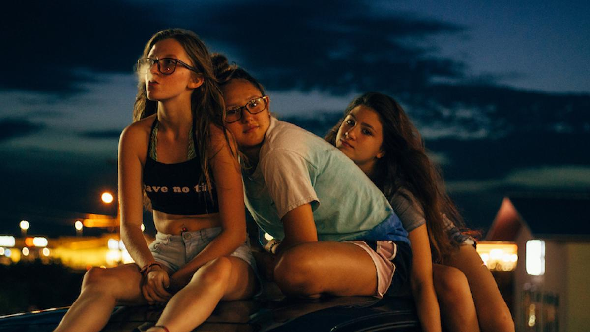 Three teenage girls sit together on the roof of a car shortly after sunset.