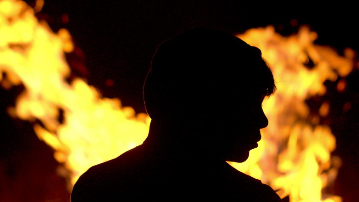 The sillouette of a young man's head and shoulders in profile, backlit by yellow-orange flames.