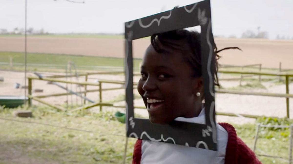 A laughing girl with a picture frame attached to her face, with fenced agricultural fields in the background.