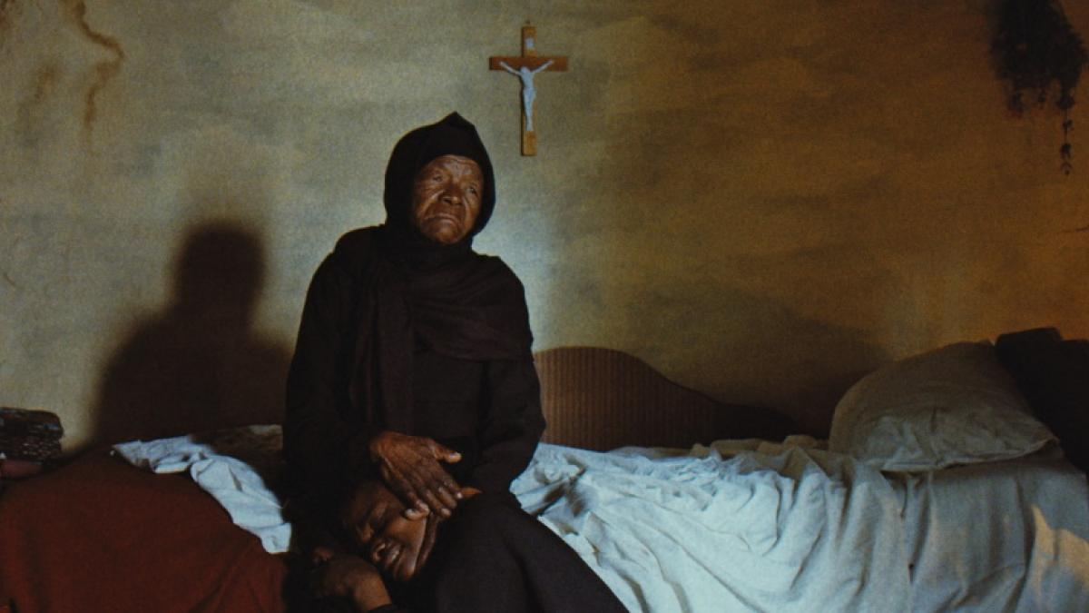 An elderly Black woman in long black robes and headscarf sits on a bed, cradling a younger Black man's head in her lap.