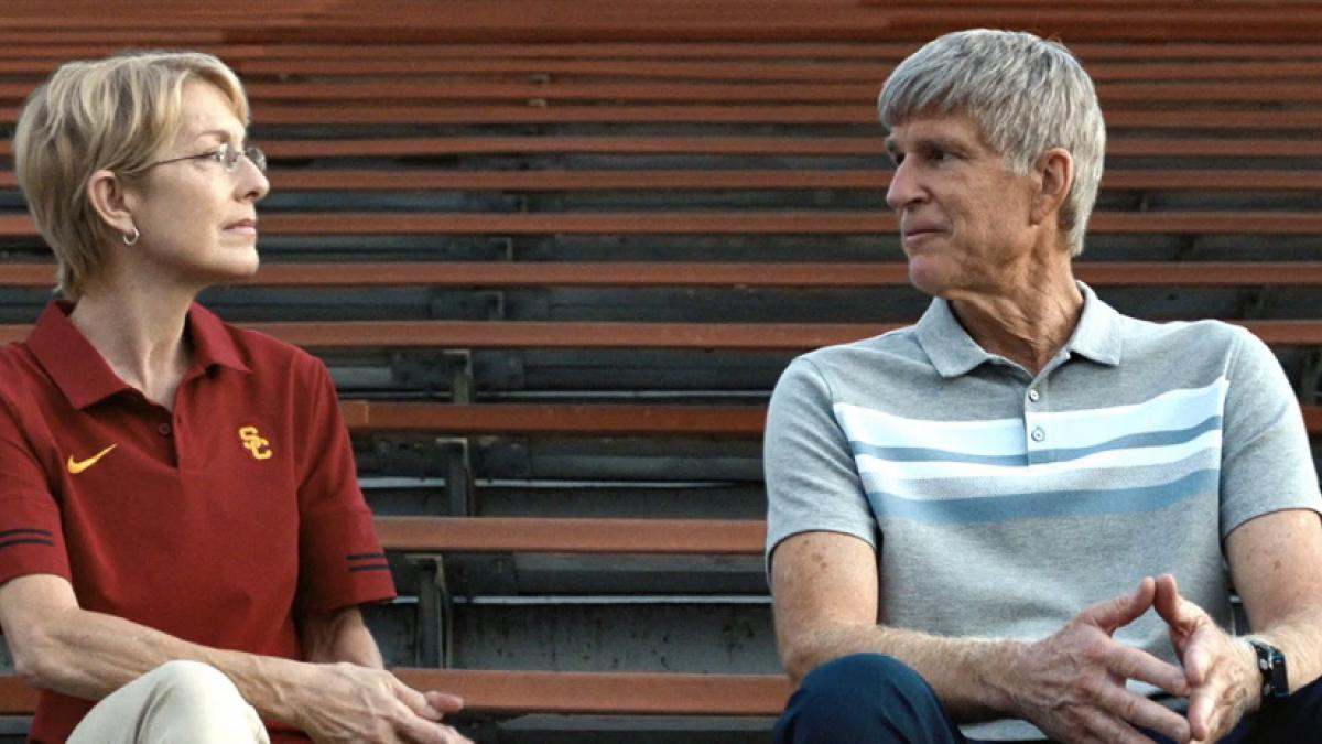 An older woman in a red polo shirt and older man in gray striped polo shirt sit side-by-side on sports bleachers, looking at one another.