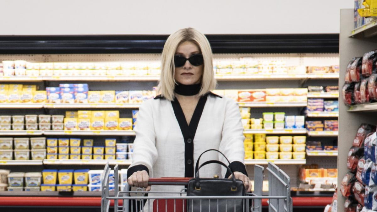 An elegant woman in a white coat in sunglasses pushing a shopping cart through a grocery store.