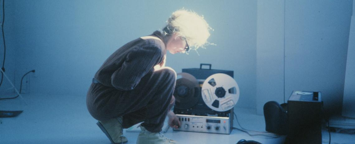 A woman crouches in profile, inspecting a real-to-real audio device.