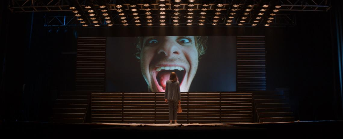 A woman standing in front of a giant screen, which is showing an image of a man's laughing face.